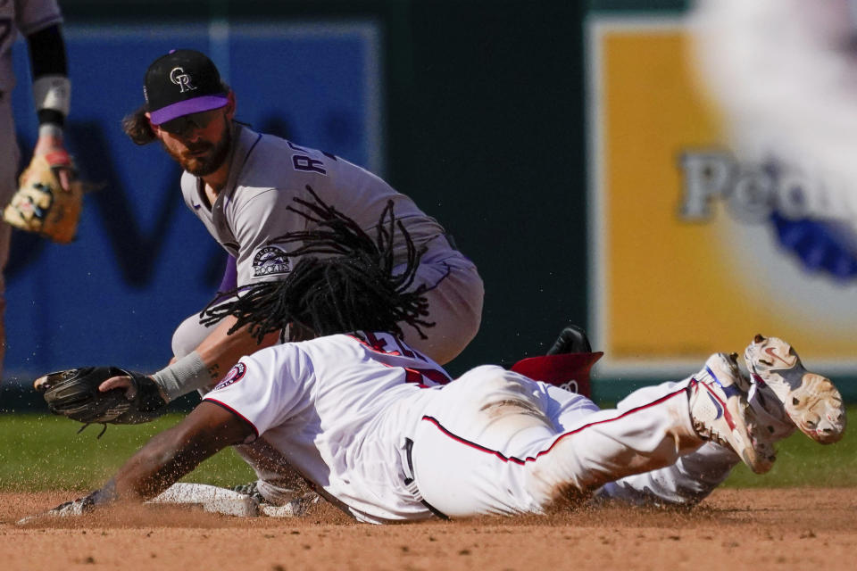 Colorado Rockies shortstop Brendan Rodgers, top, tags out Washington Nationals Josh Bell at second base during the eighth inning of a baseball game at Nationals Park, Sunday, Sept. 19, 2021, in Washington. (AP Photo/Andrew Harnik)