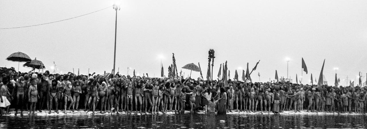 ALLAHABAD, INDIA - JANUARY 14: (EDITORS NOTE: Image was created using the iPhone panoramic application) Naga sadhus line up on the banks of Sangam during the auspicious bathing day of Makar Sankranti of the Maha Kumbh Mela on January 14, 2013 in Allahabad, India. The Maha Kumbh Mela, believed to be the largest religious gathering on earth is held every 12 years on the banks of Sangam, the confluence of the holy rivers Ganga, Yamuna and the mythical Saraswati. The Kumbh Mela alternates between the cities of Nasik, Allahabad, Ujjain and Haridwar every three years. The Maha Kumbh Mela celebrated at the holy site of Sangam in Allahabad, is the largest and holiest, celebrated over 55 days, it is expected to attract over 100 million people. (Photo by Daniel Berehulak/Getty Images)