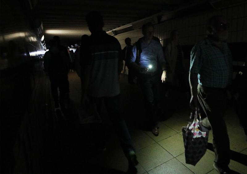 People walking in complete darkness at Clapham Junction station in London during a power cut, which has caused �apocalyptic� rush-hour scenes across England and Wales, with traffic lights down and trains coming to a standstill.