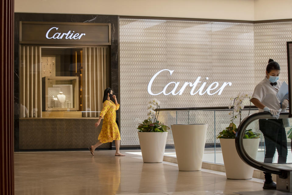 Mall employee Glenby Ramirez, right, wipes down the escalator handrail while a shopper passes by Cartier as South Coast Plaza reopens, requiring customers maintain a social distance and wear face masks at South Coast Plaza June 11, 2020 in Costa Mesa, CA.