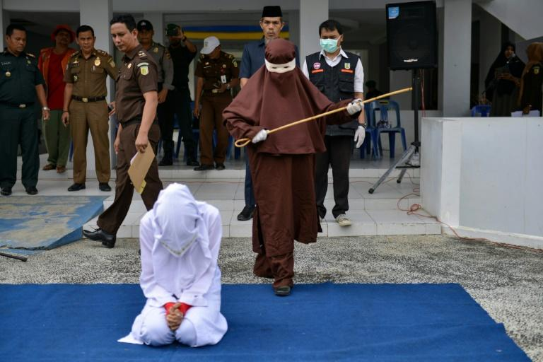 The first female flogger prepares to whip a woman in public, in Banda Aceh, Indonesia for a morality crime