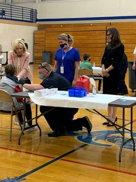 PHOTO: First lady Dr. Jill Biden holds the hand of a teenager getting vaccinated, left, as actress Jennifer Garner, right, looks on at Capital High School in Charleston, W.V., on May 13, 2021. (Katie Rogers/CNP via Polaris)