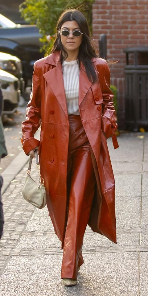 <p>Kourtney Kardashian stepped out in Calabasas while wearing a trendy leather coat with matching pants, a white ribbed top, Prada bag, and python boots.</p>