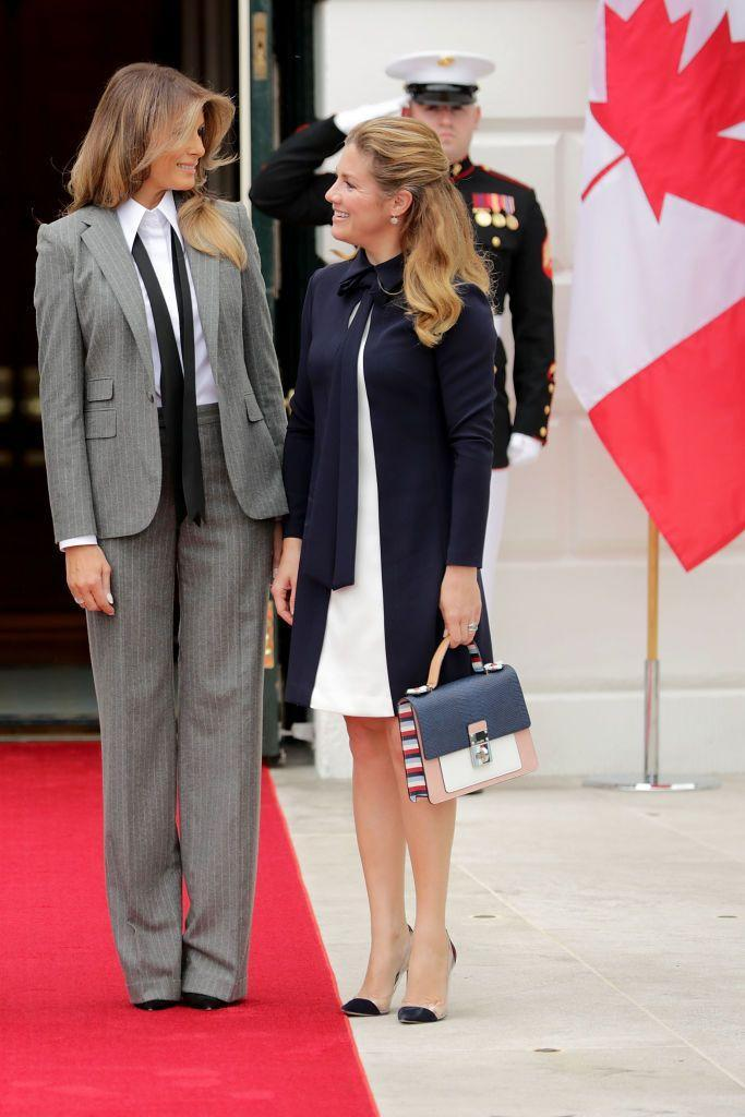 """<p>The First Lady greeted Canadian Prime Minister Justin Trudeau and his wife in a statement pantsuit—<a href=""""https://www.townandcountrymag.com/society/politics/a13101015/melania-ivanka-trump-ralph-lauren-suit/"""" rel=""""nofollow noopener"""" target=""""_blank"""" data-ylk=""""slk:a favorite style of hers"""" class=""""link rapid-noclick-resp"""">a favorite style of hers</a>. She paired with a white collared button up shirt, and a loose black tie. </p>"""