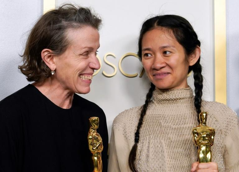 """Actress Frances McDormand and director Chloe Zhao, who both produced """"Nomadland,"""" hold the Oscar for best picture as they pose in the press room"""