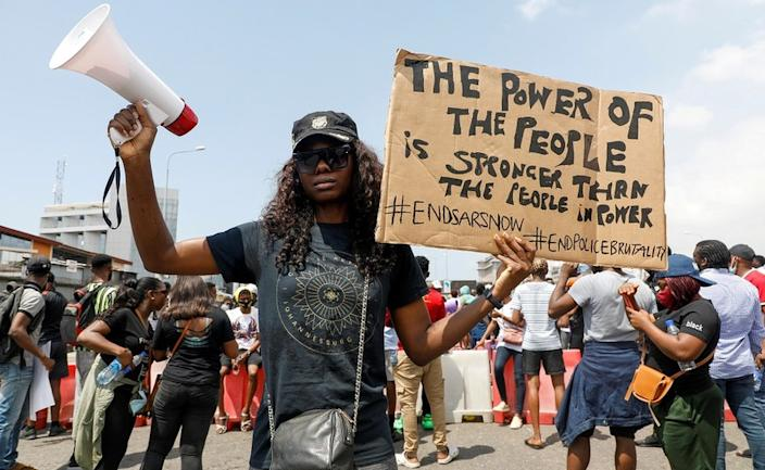 A demonstrator holds a banner during a protest against alleged police brutality, in Lagos, Nigeria