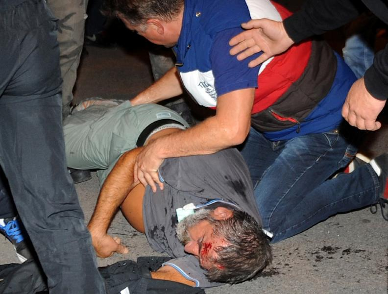 A Montenegrin opposition protester lies on the ground after clashes with police officers in Podgorica on October 18, 2015 (AFP Photo/Savo Prelevic)