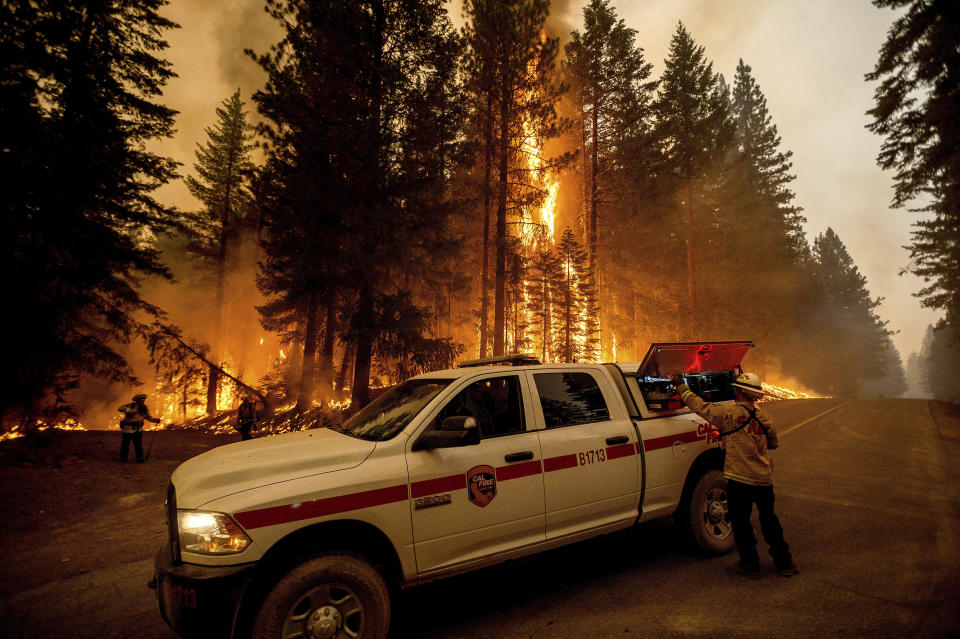 Firefighters monitor a backfire they lit to stop the Dixie Fire from spreading near Prattville in Plumas County, Calif., on Friday, July 23, 2021. (AP Photo/Noah Berger)