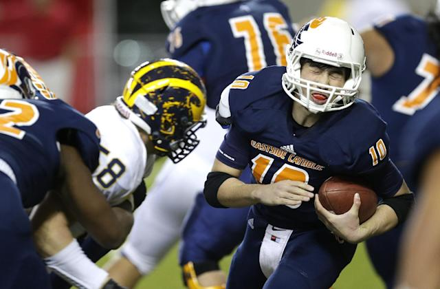 FILE - In this Dec. 6, 2013 file photo, Eastside Catholic quarterback Harley Kirsch, right, winces moments before being hit by Bellevue's Ryan Bowman, left, in the second half of the Class 3A high school football championship in Tacoma, Wash. Nearly half of parents say they're not comfortable letting their child play football amid growing uncertainty about the long-term impact of concussions, according to an Associated Press-GfK poll. A majority, however, say they haven't prevented their child from playing the game they love. (AP Photo/Ted S. Warren)