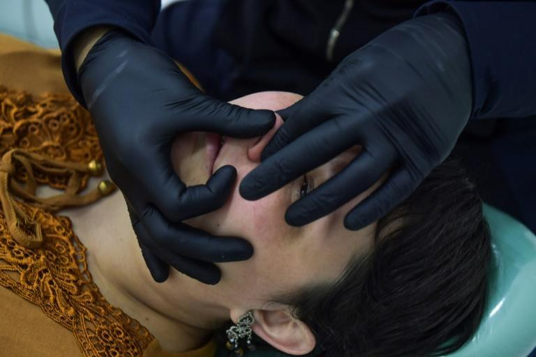 Brazilian orthodontist Thiago Aragaki gives his client Rita Meireles a facial treatment with hyaluronic acid in Sao Paulo, Brazil, on December 11, 2020