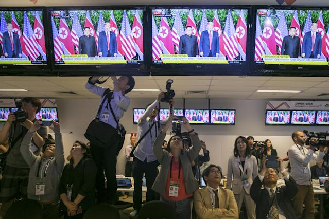 <p>Members of the media watch as television screens display a news broadcast of President Donald Trump and North Korean leader Kim Jong Un meeting at a summit, inside the media center for the DPRK-USA Singapore Summit in Singapore, on Tuesday, June 12, 2018. (Photo: Brent Lewin/Bloomberg via Getty Images) </p>