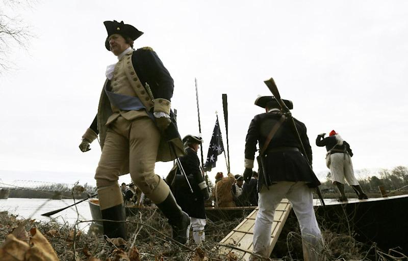 George Washington, played by John Godzieba, left, walks onto land on the New Jersey side after a crew of re-enactors crossed the Delaware River on a boat from Pennsylvania during the 61st annual re-enactment of Washington's daring Christmas 1776 crossing of the river, the trek that turned the tide of the Revolutionary War, in Washington Crossing, N.J. During the crossing 237 years ago, boats ferried 2,400 soldiers, 200 horses and 18 cannons across the river, and the troops marched eight miles downriver before battling Hessian mercenaries in the streets of Trenton. (AP Photo/Julio Cortez)