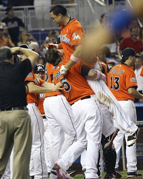 Miami Marlins' Logan Morrison (5) hoists teammate Giancario Stanton into the air after Stanton hit the game-winning grand slam against the New York Mets in the ninth inning of a baseball game in Miami, Sunday, May 13, 2012. The Marlins defeated the Mets 8-4. (AP Photo/J Pat Carter)