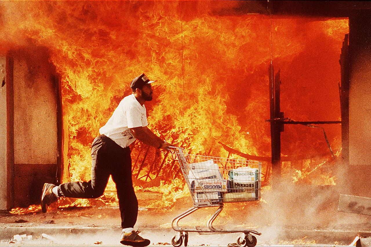 <p>A man is shown pushing a shopping cart full of diapers as he runs past a burning market (Photo: Kirk Mckoy/Los Angeles Times via Getty Images) </p>