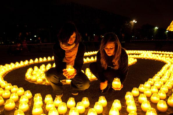 Earth Hour 2010. Two volunteers holding a candle amongst the 1600 candles, symbols of the 1600 pandas and forming the shape of a 60 to celebrate Earth Hour, place Jacques Rueff, Eiffel Tower, Paris, France.