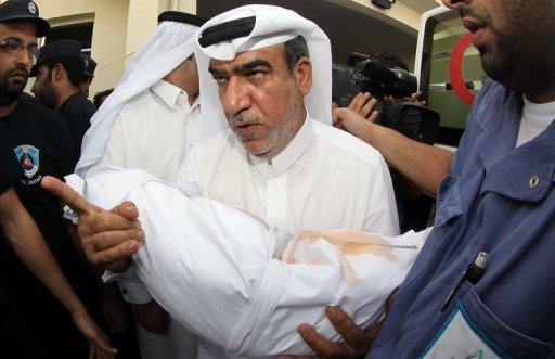 A Qatari man carries the body of his child, who died in a blaze that whipped through a shopping mall in Doha on Monday. Firefighters in Qatar told Wednesday how they tried to rescue 13 children trapped by a blaze in a mall nursery but by the time they reached the toddlers most were dead, huddled in the arms of two fellow firemen who perished during the rescue attempt