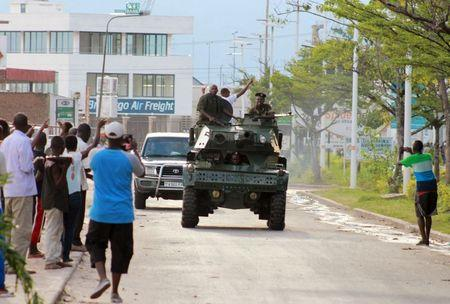 Soldiers patrol the streets in a military vehicle as civilians celebrate in Burundi's capital Bujumbura