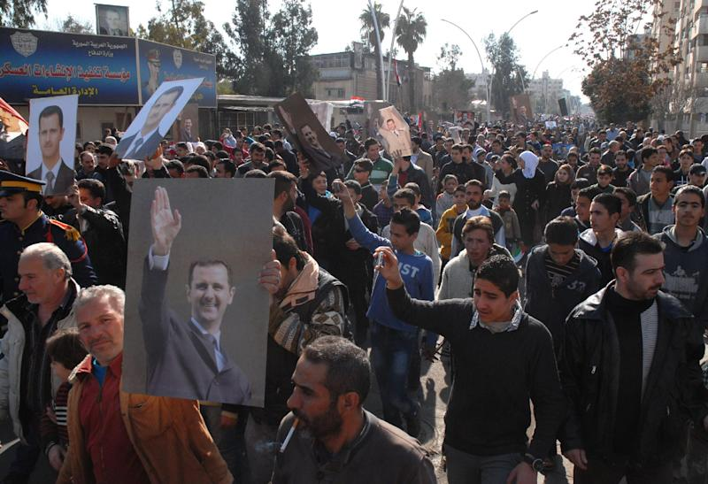 In this photo released by the Syrian official news agency SANA, pro-government Syrian protesters hold portraits of Syrian President Bashar Assad as they march during a demonstration at Kafar Souseh neighborhood in Damascus, Syria, Friday, Feb. 7, 2014. The Syrian government announced it will take part in a second round of peace talks in Geneva on Monday. The first face-to-face U.N.-hosted talks adjourned on Jan. 31. (AP Photo/SANA)