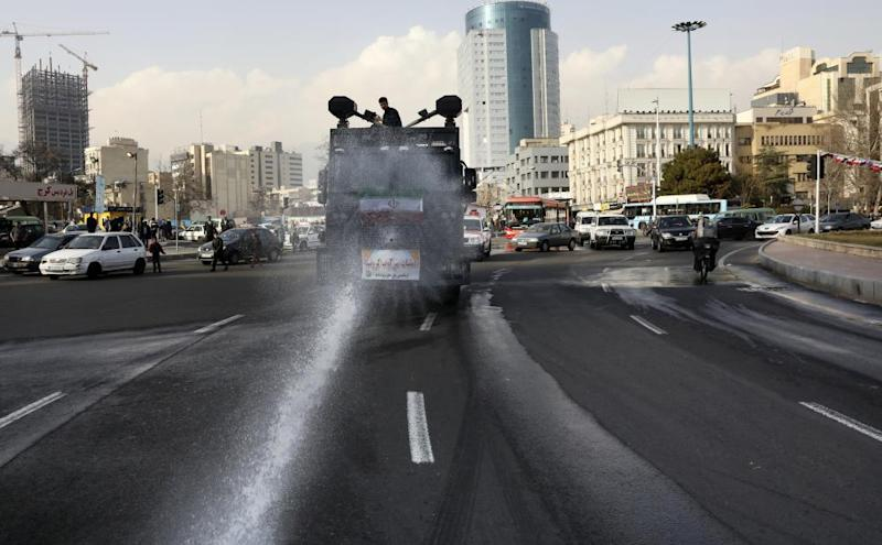 A police vehicle disinfects streets against coronavirus in Tehran, Iran