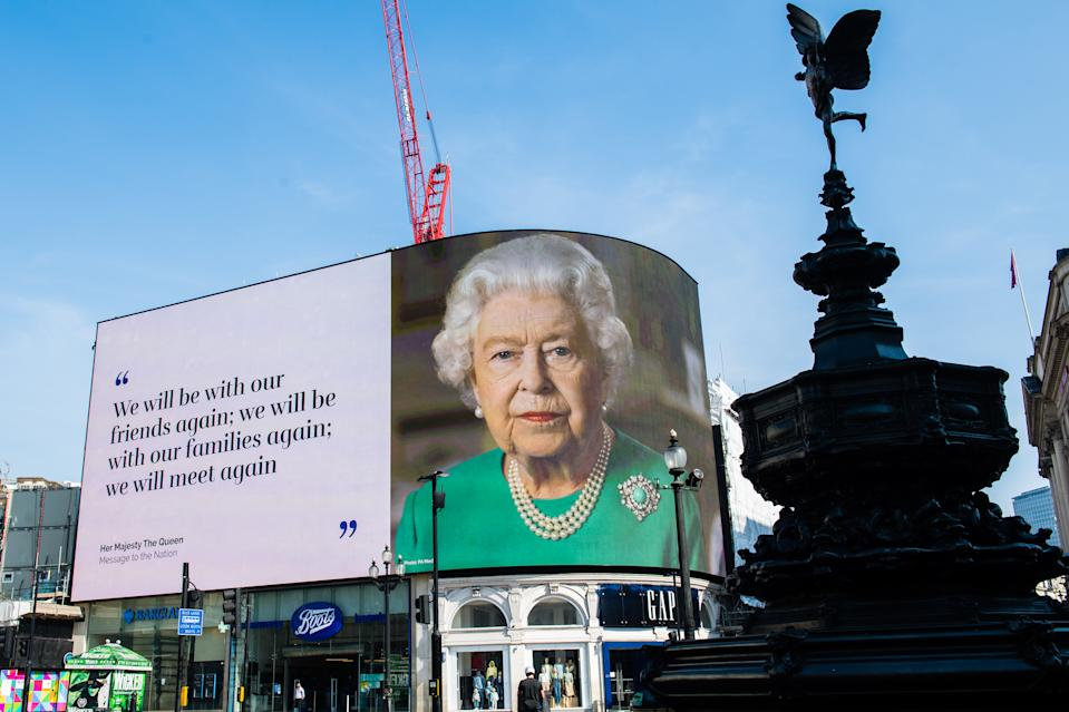 LONDON, ENGLAND - APRIL 10: An image of Queen Elizabeth II and quotes from her broadcast to the nation in relation to the coronavirus epidemic are displayed on screens in Piccadilly Circus on April 10, 2020 in London, England. (Photo by Samir Hussein/WireImage,)