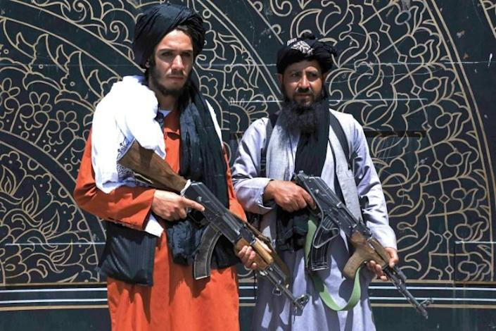 Taliban fighters stand guard in front of the provincial governor's office in Herat, where the insurgents issued amnesty letters to Afghan soldiers