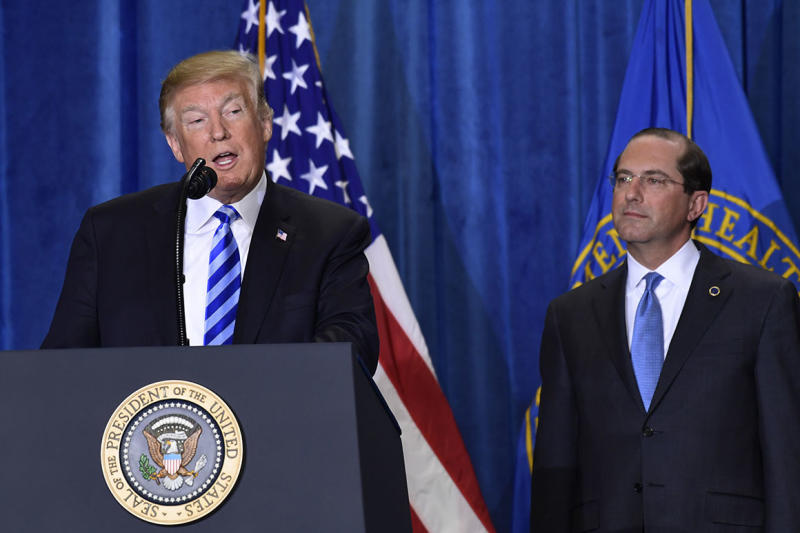 President Donald Trump, left, standing with Health and Human Services Secretary Alex Azar, right, talks about drug prices during a visit to the Department of Health and Human Services in Washington, Thursday, Oct. 25, 2018. (AP Photo/Susan Walsh)