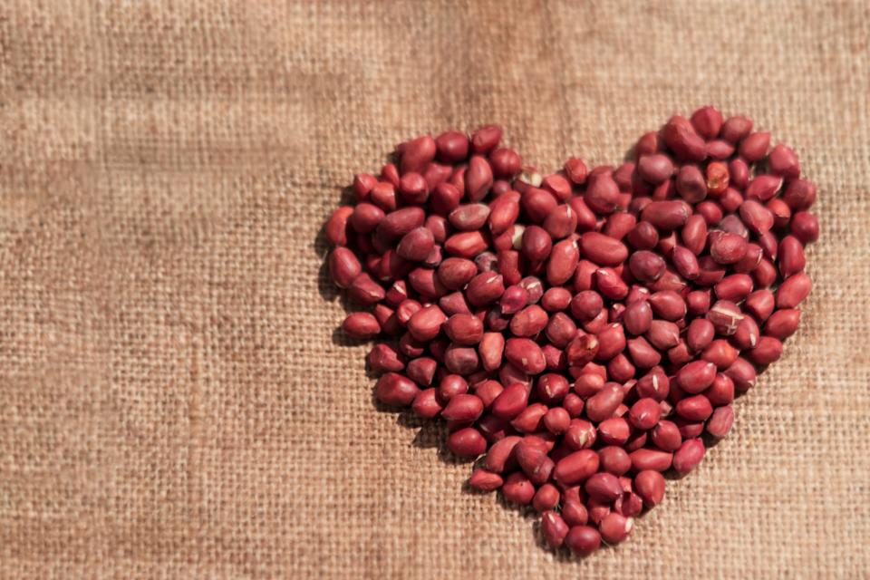 Raw unpeeled peanuts forming a heart shape defying a healthy heart on a burlap or sack cloth with copy space. Background photo for good healthy life.