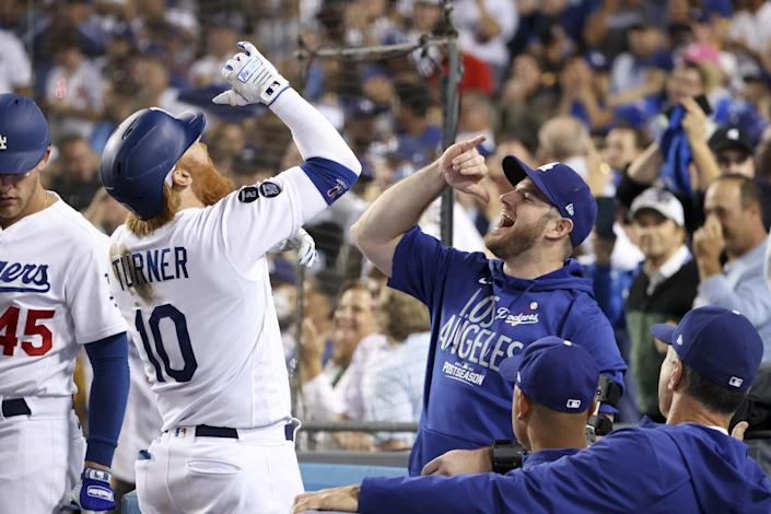 Los Angeles Dodgers' Justin Turner, left, celebrates with Max Muncy after hitting a solo home run