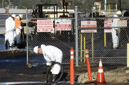 Workers clean up spilled oil at a facility in Los Angeles, May 15, 2014. REUTERS/Phil McCarten