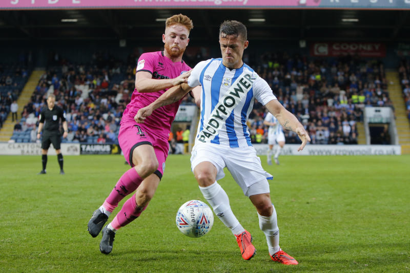 ROCHDALE, ENGLAND - JULY 17: Jonathan Hogg of Huddersfield Town is challenged by Callum Camps of Rochdale during the game between Rochdale and Huddersfield Town at the Crown Oil Arena on July 17, 2019 in Rochdale, England. (Photo by John Early/Getty Images)