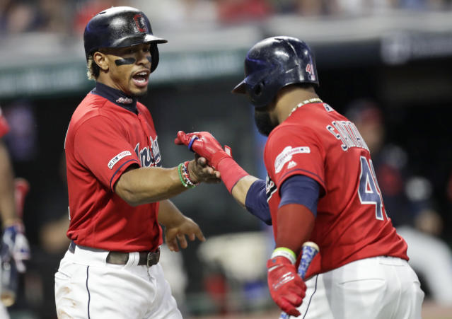Cleveland Indians' Francisco Lindor, left, congratulates Carlos Santana after Santana hit a sacrifice fly in the first inning in a baseball game against the Detroit Tigers, Thursday, Sept. 19, 2019, in Cleveland. Lindor scored on the play. (AP Photo/Tony Dejak)