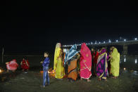 Indian Hindu devotees perform evening rituals on the banks of the Sarayu river in Ayodhya, India , Saturday, Nov. 9, 2019. India's Supreme Court on Saturday ruled in favor of a Hindu temple on a disputed religious ground and ordered that alternative land be given to Muslims to build a mosque. The dispute over land ownership has been one of the country's most contentious issues. (AP Photo/Rajesh Kumar Singh)