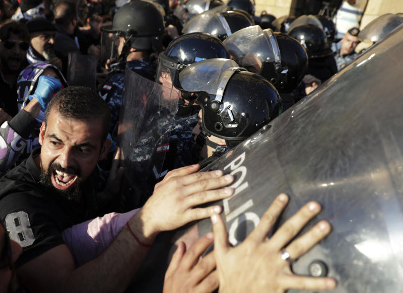 Anti-government protesters scuffle with riot police during a protest in downtown Beirut, Lebanon, Tuesday, Nov. 19, 2019. Scuffles have broken out in central Beirut as hundreds of anti-government protesters tried to prevent lawmakers from reaching Parliament. (AP Photo/Hassan Ammar)
