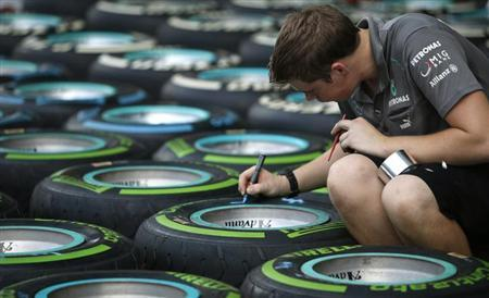 "A Petronas Formula One team crew makes markings on rows of ""Intermediate"" (green) and ""Full Wet"" Pirelli race tyres at the pit ahead of the Singapore F1 Grand Prix September 19, 2013. REUTERS/Tim Chong"