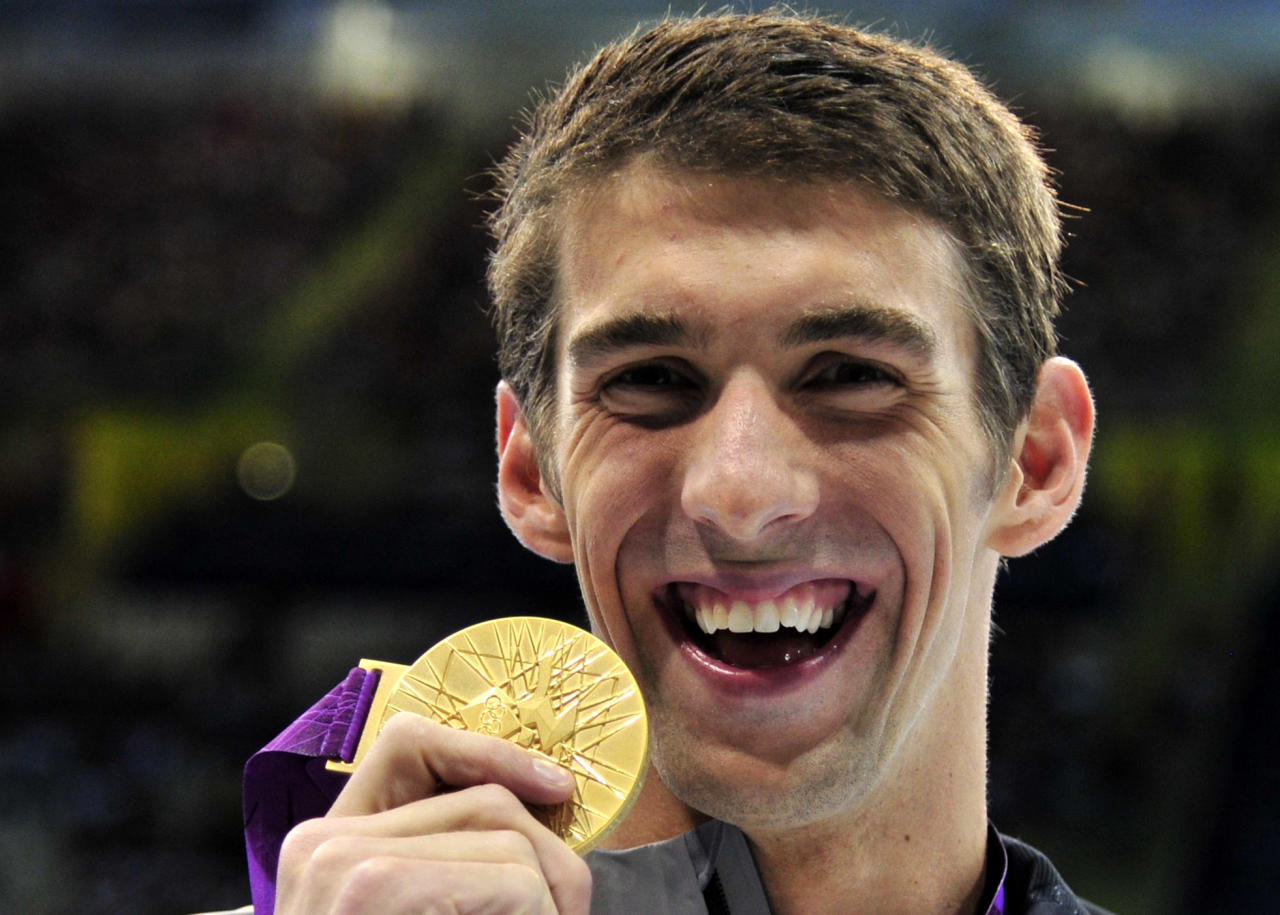 Michael Phelps of the U.S. celebrates with his gold medal at the men's 100m butterfly victory ceremony at the London 2012 Olympic Games at the Aquatics Centre August 3, 2012. REUTERS/Toby Melville (BRITAIN  - Tags: SPORT OLYMPICS SPORT SWIMMING)