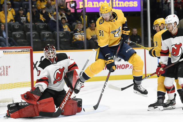 Nashville Predators left wing Austin Watson (51) jumps out of the way as New Jersey Devils goaltender Louis Domingue (70) gloves a shot during the second period of an NHL hockey game Saturday, Dec. 7, 2019, in Nashville, Tenn. (AP Photo/Mark Zaleski)