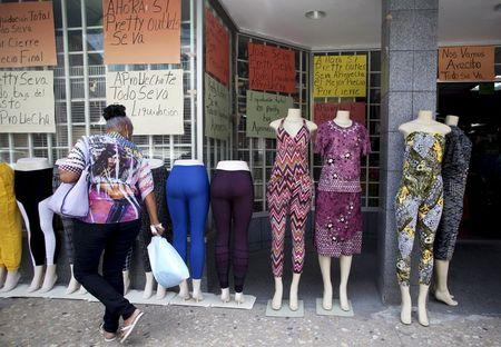"""A woman walks past clothes for sale and signs reading """"Closing down sale"""" in Arecibo, Puerto Rico, June 29, 2015.  REUTERS/Alvin Baez-Hernandez"""