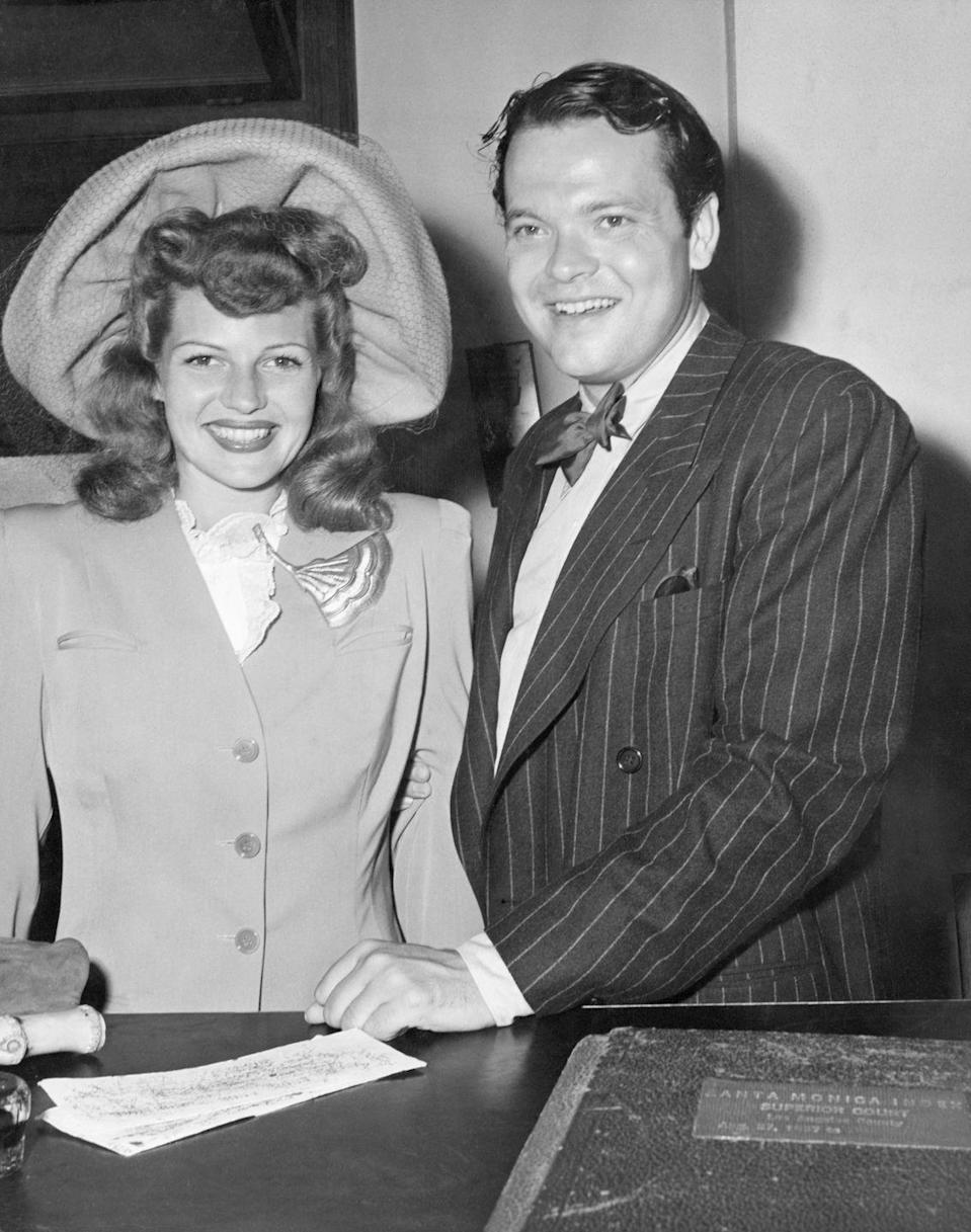 <p>Rita Hayworth look overjoyed receiving her marriage license in Santa Monica, California with Orson Welles. For her second wedding, the bride wore a simple suit and veiled hat with a fan brooch on her lapel.</p>