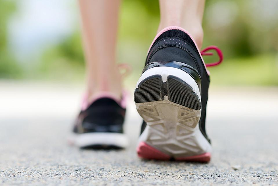 Low Section Of Woman Wearing Shoes Walking On Road - stock photo