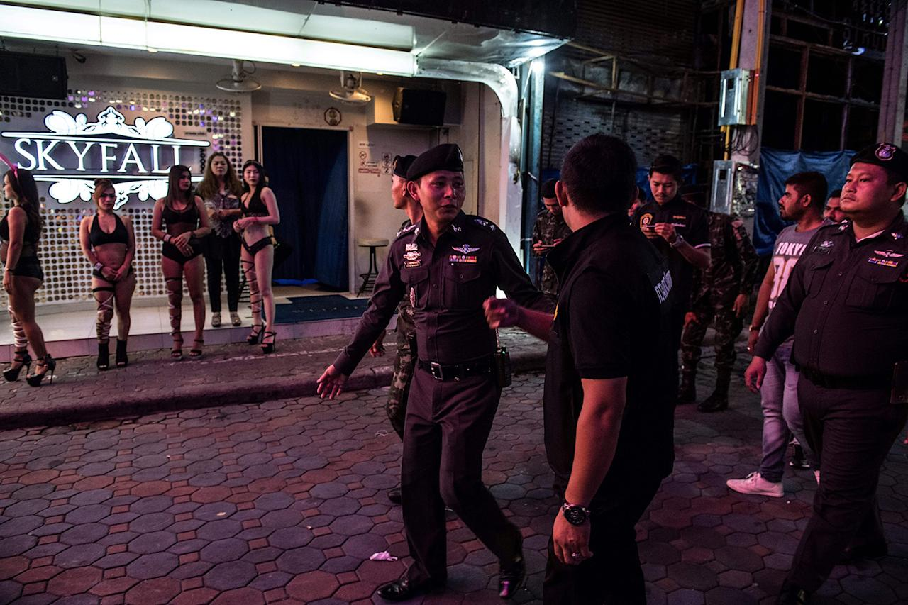 <p>Police Lt. Col. Sulasak Kalokwilas leads policemen and soldiers past a group of young women, enticing customers to a bar, as they patrol Walking Street in Pattaya. (Photo: Roberto Schmidt/AFP/Getty Images) </p>