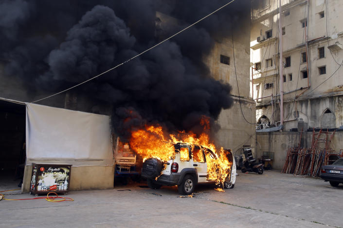 A police car set on fire by anti-government protesters burns in the northern city of Tripoli, Lebanon, Tuesday, April 28, 2020. Hundreds of angry Lebanese took part Tuesday in the funeral of a young man killed in riots overnight in Tripoli that were triggered by the crash of Lebanon's national currency that sent food prices soaring. (AP Photo/Bilal Hussein)