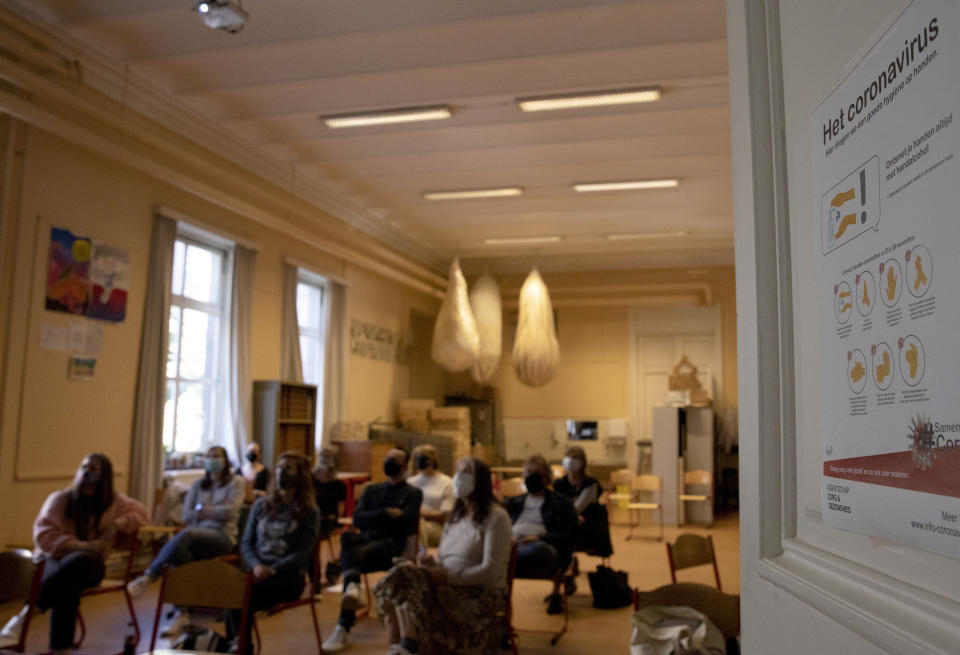 Teachers sit in a classroom with protective face masks as they watch a video conference presentation from school director Karin Heremans, outlining the new school year coronavirus, COVID-19 measures, at the Atheneum high school in Antwerp, Belgium, Monday, Aug. 31, 2020. Students return to school in Belgium on Tuesday, Sept. 1, with measures in place regarding social distancing and the wearing of masks to protect against the spread of coronavirus, COVID-19. (AP Photo/Virginia Mayo)