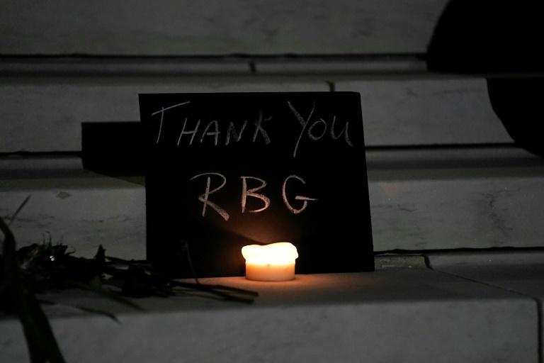 A sign and a candle form a makeshift memorial on the steps of the Supreme Court building, in honor of Ruth Bader Ginsburg
