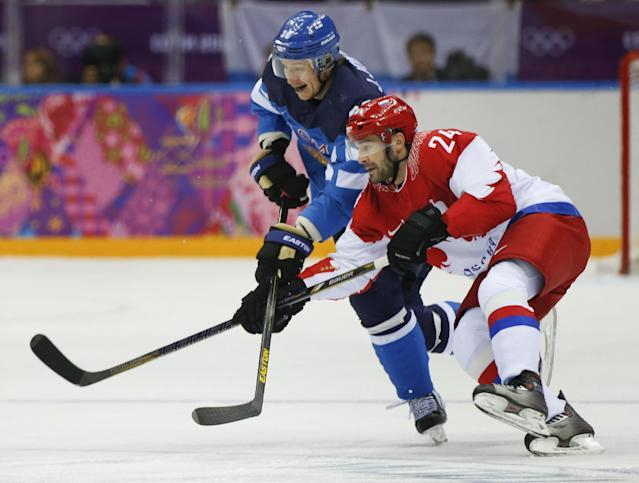 Russia forward Alexander Popov races after the puck against Finland forward Jussi Jokinen during the first period of a men's quarterfinal ice hockey game at the 2014 Winter Olympics, Wednesday, Feb. 19, 2014, in Sochi, Russia. (AP Photo/Julio Cortez)