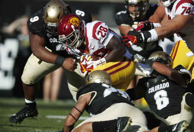 "USC running back Aca'Cedric Ware, center, is tackled after a short gain by, from left, Colorado nose tackle Javier Edwards, linebacker Drew Lewis and defensive back <a class=""link rapid-noclick-resp"" href=""/ncaaf/players/242978/"" data-ylk=""slk:Evan Worthington"">Evan Worthington</a> in the first half of an NCAA college football game Saturday, Nov. 11, 2017, in Boulder, Colo. (AP Photo/David Zalubowski)"