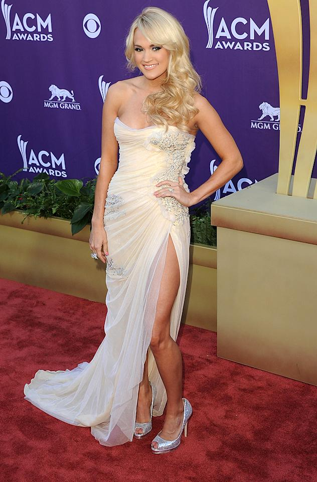 "Carrie Underwood stunned in an ethereal strapless gown at the 47th annual Academy of Country Music Awards at the MGM Grand Garden Arena in Las Vegas on Sunday. And from the looks of that pose — very reminiscent of <a target=""_blank"" href=""http://omg.yahoo.com/blogs/runway/angelina-jolie-responds-oscar-dress-leg-phenomena-224338844.html%20"">Angelina Jolie's now-famous stance</a> at the Oscars — she knows it! The star will perform her song ""Good Girl"" at the show and is nominated for Female Vocalist of the Year and Vocal Event of the Year."