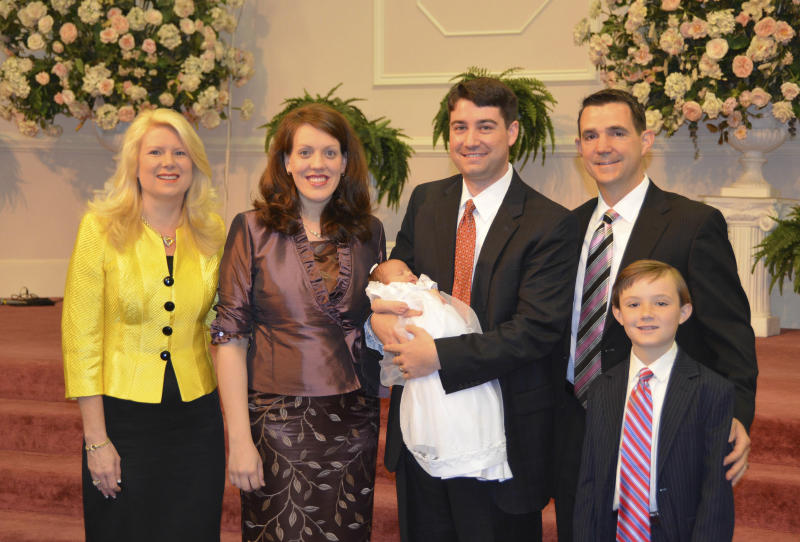 FILE - In this 2012 photo provided by a former member of the church, Jeffrey Cooper holds his infant daughter at her 2012 baby dedication at the Word of Faith Fellowship compound in Spindale, N.C.At second right is Frank Webster, an assistant North Carolina prosecutor who is married to church leader Jane Whaley's daughter, Robin, left. At right is Frank Webster's son, Brock. At second left is Jeffrey Coopers' wife, Natalie. A district attorney has asked the state to investigate two assistant prosecutors after an Associated Press story that quoted former congregants of a North Carolina church as saying the men derailed criminal probes into allegations of abuse by sect leaders. The AP story, released Monday, March 6, 2017, cited nine former Word of Faith members who said Frank Webster and Chris Back provided legal advice, helped at strategy sessions and participated in a mock trial for four congregants charged with harassing a former member. (AP Photo, File)