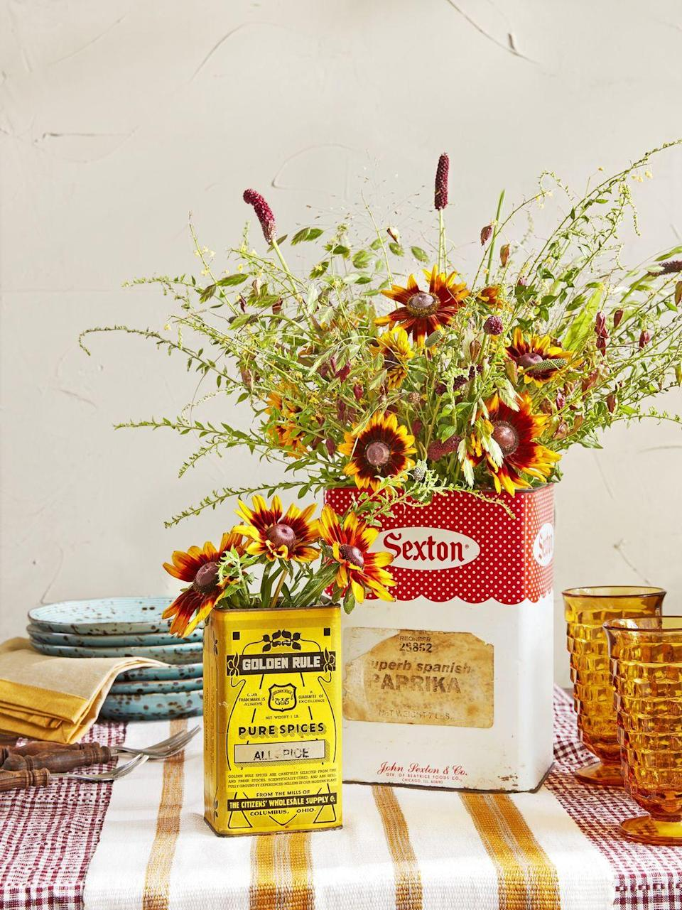 <p>Embrace the season and hunt down a few fall-colored vintage food tins the next time you go antiquing. For containers on the taller side, fill with bright, voluminous buds (like these Sanguisorba cones) to create an effortless centerpiece. As for smaller tins, keep the look casual with a looser arrangement. </p>
