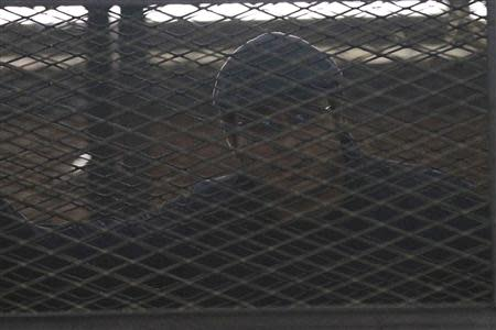 Activist Ahmed Maher stands behind bars at a court in Cairo