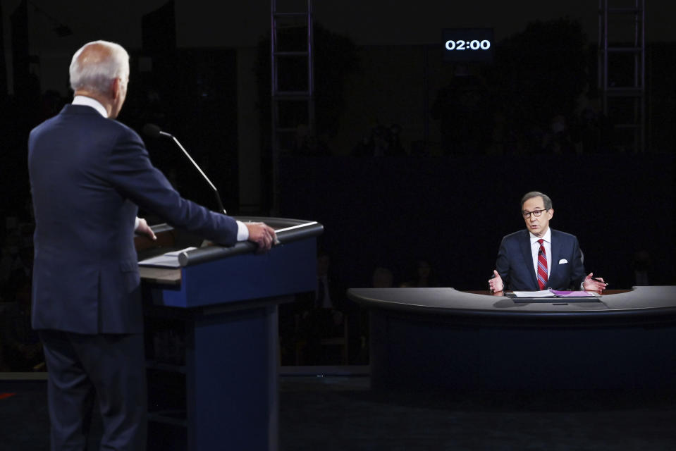 FILE - Moderator Chris Wallace of Fox News speaks as Democratic presidential candidate former Vice President Joe Biden listens during the first presidential debate in Cleveland on Sept. 29, 2020. Leaders of the Commission on Presidential Debates and moderators of all three debates gathered for a remote debrief Monday night. Two takeaways: increased early voting means the commission is considering earlier debates, and the mute button may be here to stay. (Olivier Douliery/Pool vi AP, File)